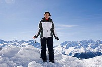 Portrait of a teenage girl standing in a snowy mountain landscape and smiling, Switzerland