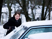 Mid adult woman cleaning windshield of a car with an ice scraper