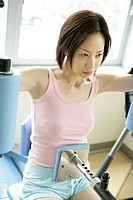 A young woman exercising for abs and shoulders on the latest equipment in the gym