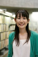 A young woman stands near the book shelves as she smiles at the camera