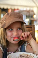 A smiling girl eating a strawberry.