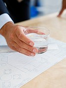 A glass of water in a hand in an office.