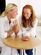 Two young women drinking coffee.