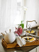 A teapot and cookies on a tray.