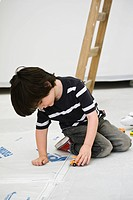 Little boy playing with toy truck on floor