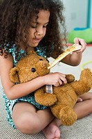 Little girl feeding teddy bear pizza