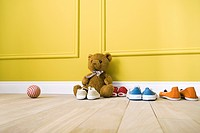 Teddy bear sitting on floor with several pairs of shoes, ball nearby