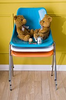 Teddy bears sitting face to face on stack of chairs