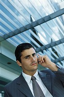 Businessman standing outside office building using cell phone