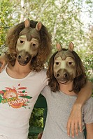 Two friends wearing horse masks, arms around each other´s shoulders