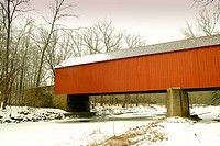 A red covered bridge adds life to a lifeless winter scene, Pennsylvania, USA