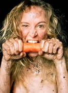 A wild woman eating a carrot.