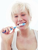A Scandinavian teenage girl brushing her teeth.