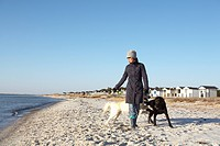 A woman with two dogs on a beach Sweden.