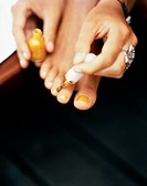 A woman painting her toe nails close_up.