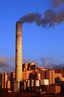 Smoke rises from the chimney of a factory