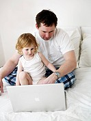 Father and daughter in front of a laptop Sweden