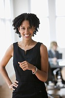 Mixed race businesswoman smiling with hand on hip