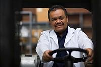 Hispanic man driving forklift