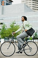Mixed race businessman riding bicycle in city