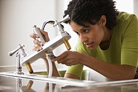 Mixed race woman installing faucet