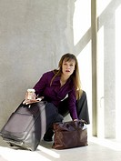 Business woman with baggage holding a cup of coffee