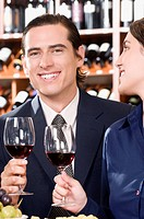 Business couple holding wine glasses and smiling