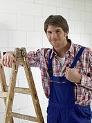Man wearing work wear is standing next to a ladder