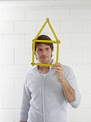 Man with a folding rule looking like a house