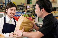 Sales clerk giving a grocery bag to a costumer in a supermarket