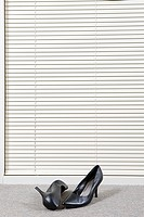 Pair of high heeled shoes in front of venetian blinds