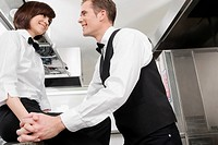 Waiter and waitress romancing in the kitchen
