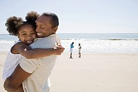 Father and daughter hugging on a beach