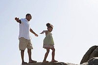 Father and daughter walking on rocks
