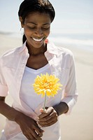 Woman holding flower on a beach