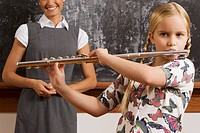 Schoolgirl playing a flute in a classroom
