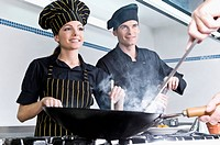 Female and a male chef cooking food in the kitchen