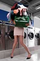 Woman carrying a laundry basket in a laundromat
