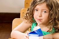 Schoolgirl drinking juice in a classroom