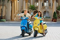 Couple sitting on mopeds, Biltmore Hotel, Coral Gables, Florida, USA