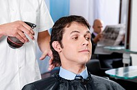Barber spraying water on a man´s hair