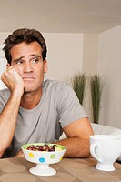 Man frowning at a bowl of fruits