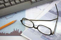 Glasses resting on financial documents on an office desk