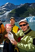 Young girl licks glacier ice while being held by her parents on the deck of the Klondike Express tour boat, Prince William Sound, Alaska