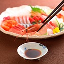 Prawn being held in chopsticks over soy sauce