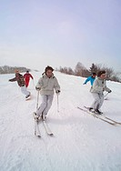 Group of people skiing and snowboarding down a slope