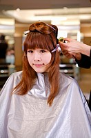 Young woman having her hair curled, Hair Salon