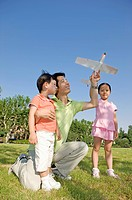 Family, father and two children playing toy airplane in a park
