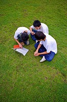 Three boys sitting on the lawn and using laptop, Teenager