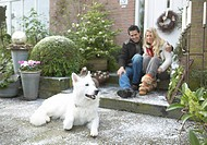 Couple with dog in front of house